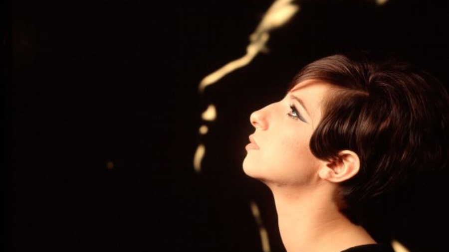 Profile of singer/actress Barbra Streisand in front of  blow-up of herself also in profile.